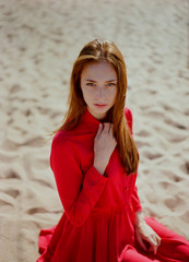 Portrait of the beautiful woman in red dress looking at camera