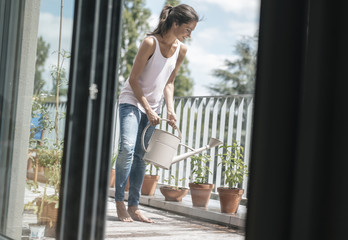 Smiling woman on balcony watering plants