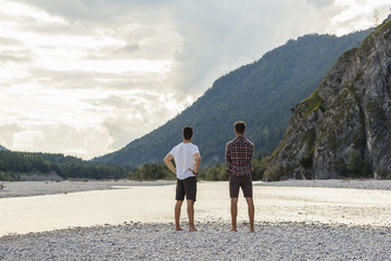 Germany, Bavaria, back view of two friends looking at view at riverside