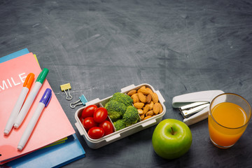 Lunch box with vegetables for a healthy school lunch on wooden table