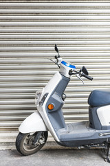 Scooter parked in front of a garage door