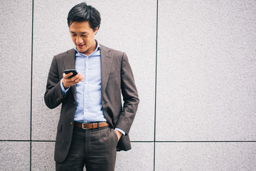 Asian business man looking at his cellphone while standing in front of a wall