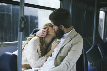 Young couple kissing in a bus