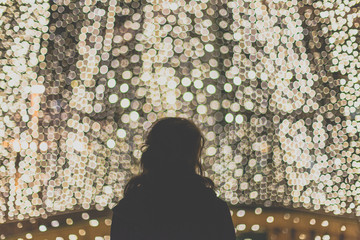 Pretty girl standing by a wall of lights