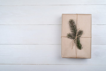 Christmas background with one gift box wrapped in kraft paper with fir tree branch on white wooden background, free space. Holiday greeting card, copy space. Flat lay, top view