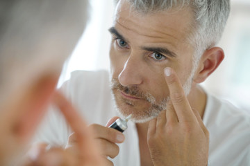 Portrait of middle-aged man applying eye concealer