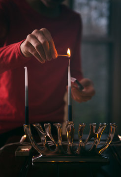 Lighting candle on the first night of Hanukkah holiday