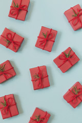 Small red decorated Christmas gifts scattered on blue background
