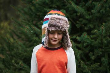 portrait of a boy in a warm, winter hat in front of a fir tree