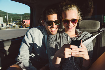 Guy and girl using smart phone in the backseat of a car.