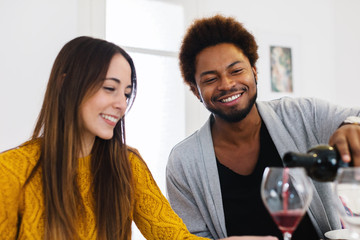 African american young man serving red wine to her friend.