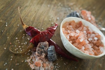 Himalayan salt with spices on wooden table