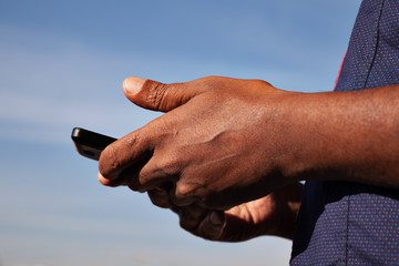 black men's hands holding phone