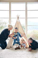 Family playing in teepee tent in living room together.