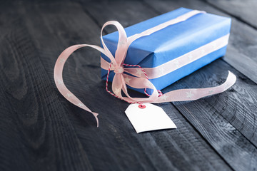 Gift box with a blank tag - Classy blue gift, tied with pink ribbon and bow, with an empty label tied to it, on an old wooden table.