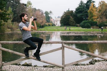 Young man takes pictures at the park with a reflex