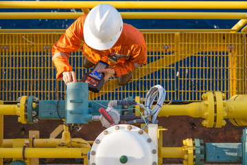 Offshore oil rig worker calibrating coriolis digital flow meter by using hand held communicator to connect between devices, instrument and electrical service of oil and gas energy business.