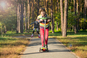 The boy is riding a scooter, followed by a girl with pigtails on rollers.