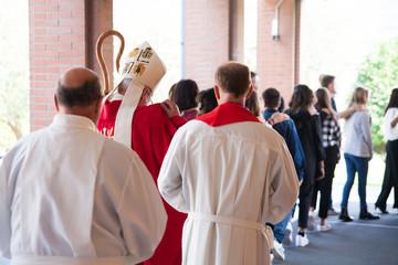 Vescovo che si avvia verso la chiesa con i suoi fedeli per la cresima