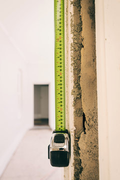 measuring tape in doorway, with architrave hanging off