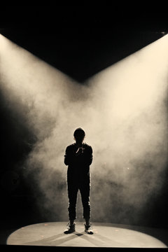 Silhouette of singer on stage in fog