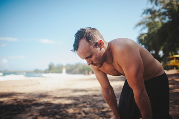 Healthy young shirtless man recovering after hard workout