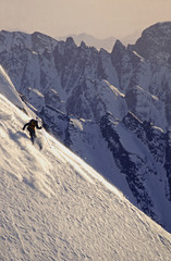 Adult male skiing a steep powder slope in the mountains