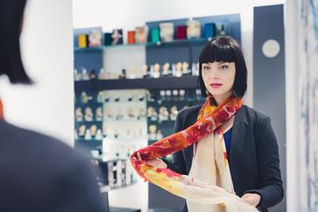 Woman looking for a new scarf inside a shop