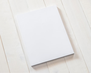 Blank A4 size book cover mockup template with page front side paperback on white surface on wood table