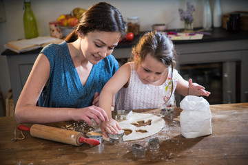 A mom and her little daughter preparing pastry in the kitchen.