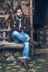 young bearded man sitting in front of an old rustic burk mulch cabin