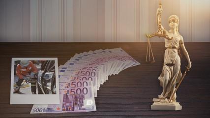 Gericht - viele Geldscheine, ein Foto von einem Verkehrsunfall und eine weiße Justitia Statue