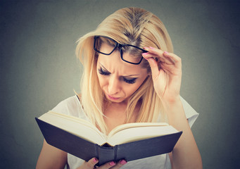 Young woman with glasses suffering from eyestrain after reading a book