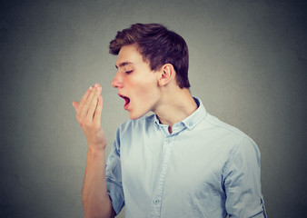 man checking his breath with hand.