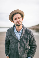 Portrait of stylish man wearing a hat and cardigan on the beach.