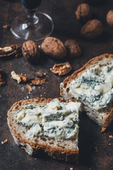 Slice of bread with blue cheese, wine and wallnuts