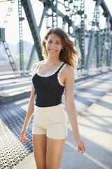 Young female walking across bridge smiling