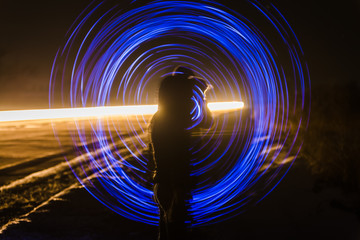 blur or defocuset abstract pgoto of artistic light on long exposure with a girl in winter clothes in the foreground