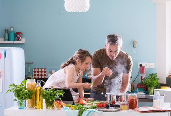 Daddy and his little daughter cooking a recipe in the kitchen