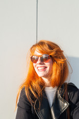 Beautiful redhead woman with sunglasses smiling.