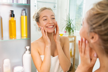 Young beautiful woman touching her face skin in bathroom. Standing in towel, looking in the mirror, laughing and having fun.  Morning skincare routine.
