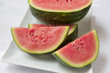 Freshly cut small watermelon on a tray.