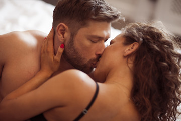Handsome man and sexy woman are  kissing in the bed.