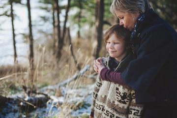 Happy grandma enjoying her grandson outside in winter - giving a kiss
