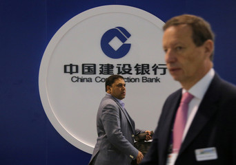 People pass the logo of the China Construction Bank at the SIBOS banking and financial conference in Toronto