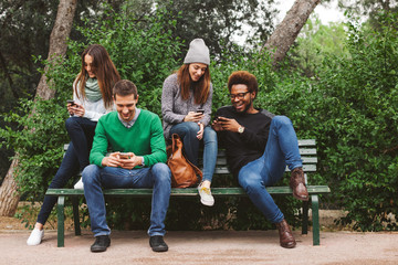 Group of friends hanging out chatting with their smartphones.