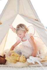 Adorable little girl playing dress up in a teepee tent in living room