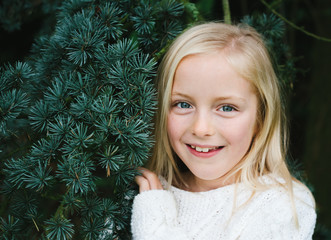A smiling little girl and a fir tree.
