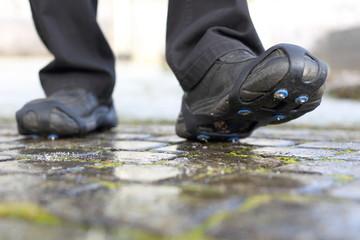 Schuhschneeketten Schuhspikes auf eisigem Weg