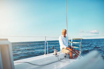 Mature man enjoying a sunny day sailing his boat